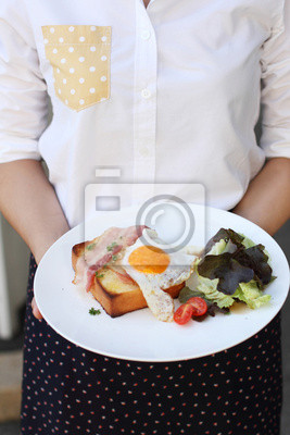 Un serviteur tient une plaque avec petit déjeuner