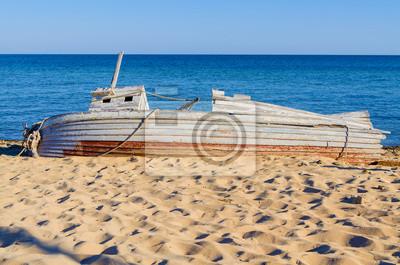 vieux bateau de pêche en bois couché sur un bord de mer