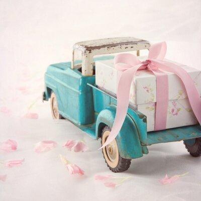 Image Vieux camion-jouet antique portant un coffret cadeau avec ruban rose