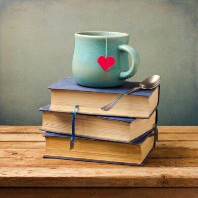 Image Vieux livres anciens et une tasse en forme de coeur sur la table en bois