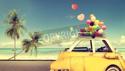 Image Voiture jaune vintage avec ballon coloré coeur sur la plage ciel bleu - concept d'amour en été et de mariage. Voyage de noces