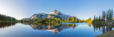 Image Volcanic mountain in morning light reflected in calm waters of lake.