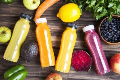 Vue de dessus des bouteilles de smoothie frais avec des fruits et légumes sur une table en bois