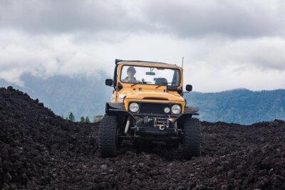 Image Vue frontalière d'un conducteur aux cheveux roux dans un véhicule hors route garé au dessus d'une vallée avec des roches volcaniques et des montagnes à Bali, en Indonésie