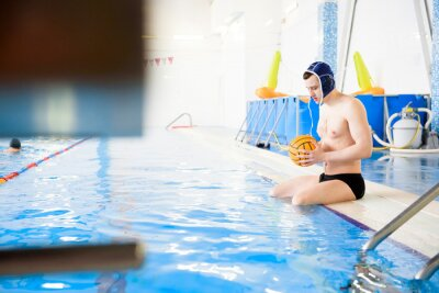 Image Water polo training. Young sportsman plays water polo in the pool.
