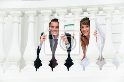 wedding couple sourire et regarder dehors du blanc balustre
