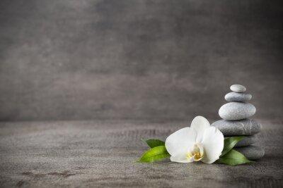 Image White Orchid et spa pierres sur le fond gris.