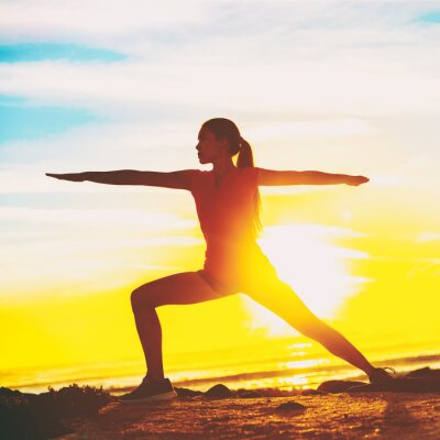 Woman doing yoga on beach. Fit girl in Warrior II pose standing in silhouette against sun flare background. Square crop for social media.