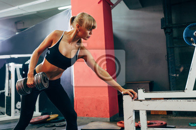 woman  in the gym doing single arm dumbbell row
