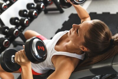 Image Woman lifting  weights and working on her chest at the  gym