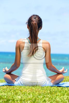 Yoga de méditation de femme sur la plage méditant par l'océan