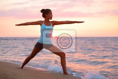 Yoga femme à méditer dans la pose de guerrier à la plage