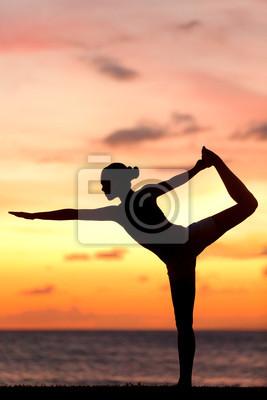 Yoga femme dans le coucher du soleil sur la plage sereine faire pose
