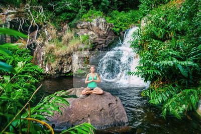 Yoga femme méditant à la cascade de forêt luxuriante à Kauai, Hawaii. Femme spirituelle priant le namaste dans une sérénité tranquille. La méditation dans la nature.