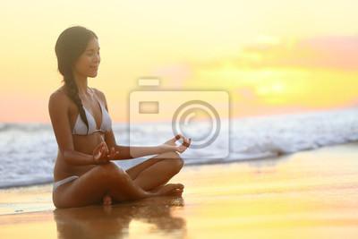 Yoga femme méditant sur la plage de coucher du soleil - détente