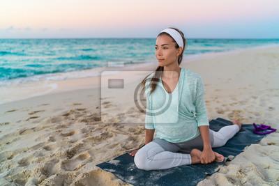Yoga femme tapis étirement de la hanche, les muscles ischio-jambiers et la région de l'aine, les muscles des jambes avec pigeon pose étirement. Fit Asiatique athlète de remise en forme sportive exerci
