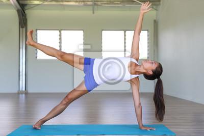 Yoga fille formation côté planche jambe soulever le noyau du corps en studio de yoga sur tapis d'exercice. Mode de vie gym fitness.