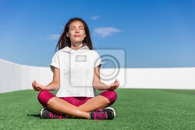 Yoga fitness femme faisant méditation d'été en plein air. Heureux athlète asiatique qui médite avant l'entraînement de la force, assis en position de lotus sur le plancher de gymnastique extérieur. Vi
