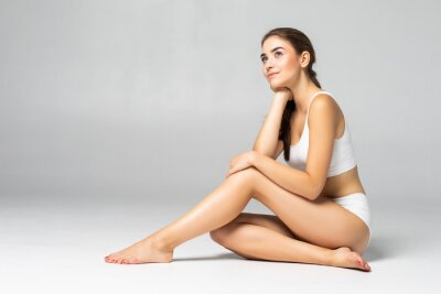 Image Young beautiful woman in cotton underwear sitting on white background