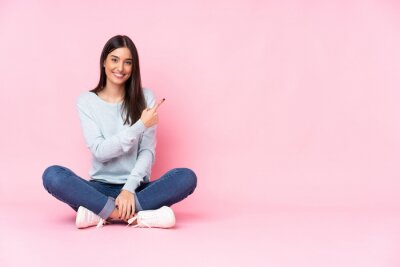 Image Young caucasian woman isolated on pink background pointing to the side to present a product