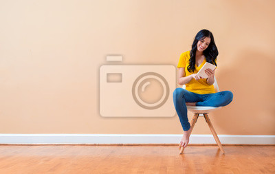 Image Young woman using her tablet sitting in a chair