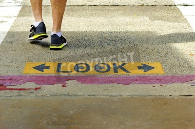 A black and yellow plastered look both ways sign on the road, with eyes drawn inside the o, which warns pedestrians to be careful of cars and bicycles at a crosswalk and a man crossing the street at a