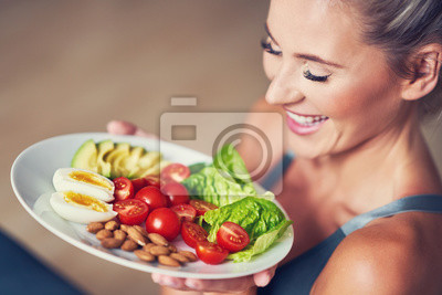 Papiers peints Adult woman eating healthy lunch and sitting on yoga mat