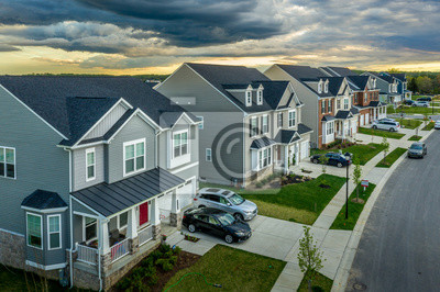 Papiers peints Aerial view of typical American new construction neighborhood street in Maryland for the upper middle class, single family homes USA real estate with dramatic sky