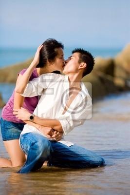 Couple Qui S Embrasse aimer le jeune couple qui sembrasse tout squating par la plage