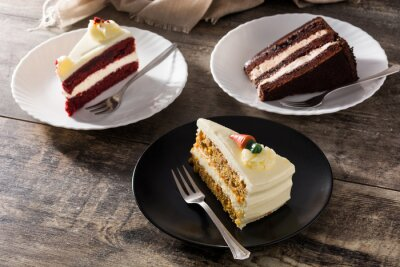 Papiers peints Assortment of sweet cake slices. Chocolate, carrot and velvet cake slices on wooden table
