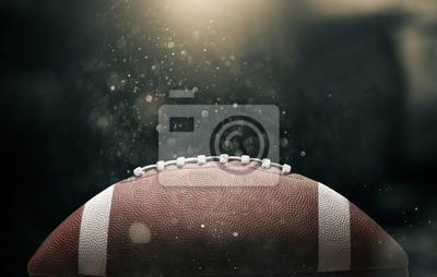 Papiers peints Ballon de football américain sur fond noir illuminé par le