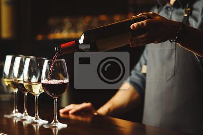 Papiers peints Barman verse du vin rouge dans des verres sur le comptoir de bar en bois