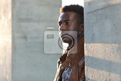 Papiers peints Beau jeune homme noir se tient entre les piliers en béton ee2f57cb7bd8