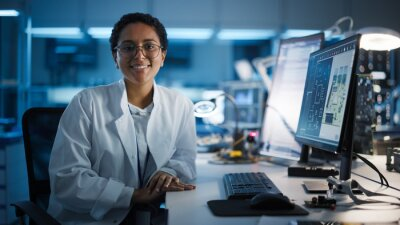 Papiers peints Beautiful Black Latin Woman Wearing Glasses Smiling Charmingly Looking at Camera. Young Intelligent Female Scientist Working in Laboratory. Technological Laboratory in Bokeh Blue as Background