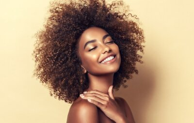 Papiers peints Beautiful black woman . Beauty portrait of african american woman with clean healthy skin on beige background.  Smiling beautiful afro girl.Curly black hair