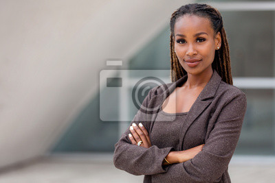 Papiers peints Beautiful female african american business woman CEO in a suit at the workplace, standing confidently with arms folded