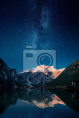Papiers peints Beautiful first light on a mountain top against stars and milky way in Lago Di Praies, Dolomites, Italy. Two image composite.