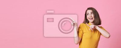 Papiers peints Beautiful healthy young woman smiling with his finger pointing and looking at on light pink banner background with copy space.