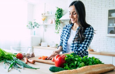 Papiers peints Beautiful young woman is preparing vegetable salad in the kitchen. Healthy Food. Vegan Salad. Diet. Dieting Concept. Healthy Lifestyle. Cooking At Home. Prepare Food. Cutting ingredients on table