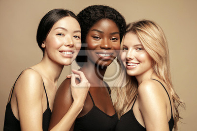 Papiers peints Beauty. Multi Ethnic Group of Womans with diffrent types of skin  together and looking on camera. Diverse ethnicity women - Caucasian, African and Asian posing and smiling against beige background.