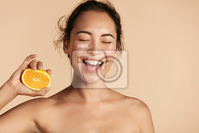 Papiers peints Beauty. Smiling woman with radiant face skin and orange portrait. Beautiful smiling asian girl model with natural makeup, healthy smile and glowing hydrated facial skin. Vitamin C cosmetics concept