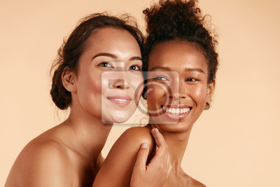Papiers peints Beauty. Smiling women with perfect face skin and natural makeup portrait. Beautiful happy asian and african girl models with different types of skin on beige background. Spa skin care concept