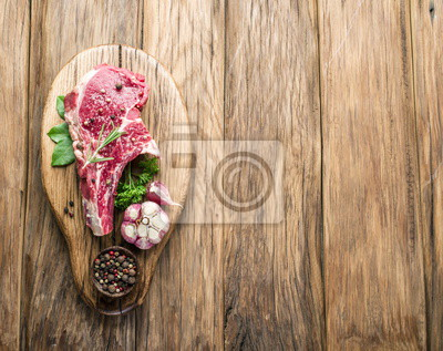 Beef steak with spices on wooden board.