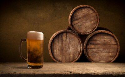 Beer barrel with beer glasses on a wooden table. The dark brown background.