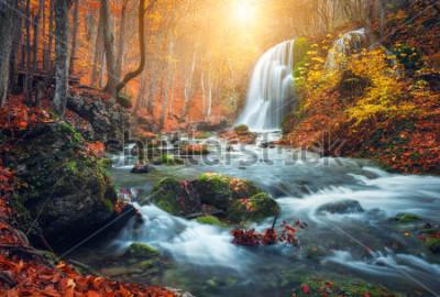 Papiers peints Belle cascade à la rivière de montagne dans la forêt d'automne coloré avec des feuilles rouges et orange au coucher du soleil. Paysage nature