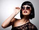 Belle femme brune avec la coiffure tourné avec des lunettes de soleil rouges 81f4f235f356