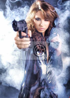 belle fille sexy tenant le pistolet. Fond de fumée