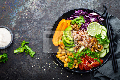Papiers peints Bol Bouddha avec riz brun, avocat, poivre, tomate, concombre, chou rouge, pois chiche, salade de laitue fraîche et noix. Manger végétarien sain, super nourriture. Vue de dessus
