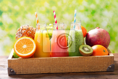 bottles of fruit juice and smoothie with fresh fruits