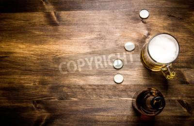 Papiers peints Bouteille de style bière, bière dans le verre et couvertures sur table en bois.